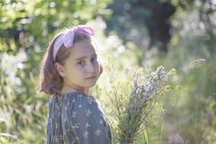 Liten flicka med en bukett av lösa blommor, stående arkivbilder