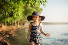 Liten flicka med en hatt vid floden i sommar arkivbild