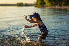 Liten flicka med en hatt vid floden i sommar arkivbilder