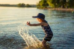 Liten flicka med en hatt vid floden i sommar royaltyfri bild