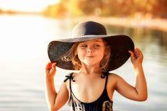 Liten flicka med en hatt vid floden i sommar royaltyfria bilder