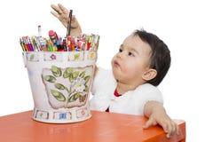 Liten flicka med en hink av blyertspennor arkivbild