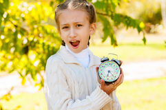 Liten flicka med en klocka i hans händer i parkera Arkivfoton