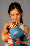 Liten flicka med en leksakhund Arkivfoto