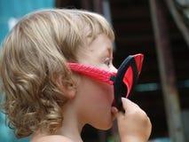 Liten flicka med en leksakmaskering arkivfoton