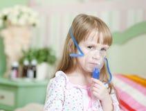 Liten flicka med en maskering för inandningar Royaltyfri Bild