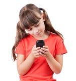 Liten flicka med en mobil telefon Royaltyfria Bilder