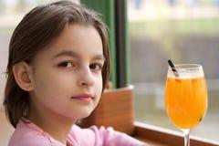 Liten flicka med en ny fruktsaft i ett exponeringsglas Royaltyfri Foto