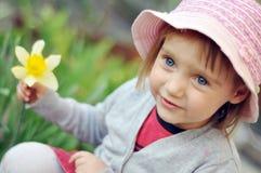 Liten flicka med en pingstlilja Arkivfoton