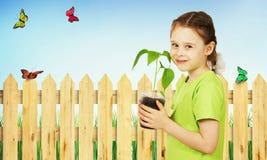 Liten flicka med en planta i krukan i trädgården Arkivbilder