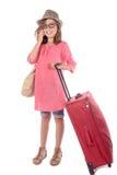 Liten flicka med en röd resväska som talar på telefonen Fotografering för Bildbyråer