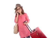 Liten flicka med en röd resväska som talar på telefonen Arkivfoton