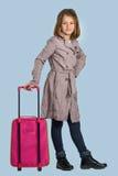 Liten flicka med en resväska förbereder sig att resa Arkivfoto