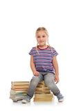 Liten flicka med en stapel av böcker Royaltyfri Bild