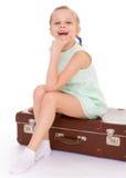 Liten flicka med en stor och mycket gammal resväska. Royaltyfria Foton