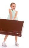 Liten flicka med en stor och mycket gammal resväska. Arkivfoton
