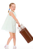 Liten flicka med en stor och mycket gammal resväska. Royaltyfri Fotografi