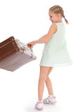 Liten flicka med en stor och mycket gammal resväska. Fotografering för Bildbyråer