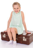 Liten flicka med en stor och mycket gammal resväska. Arkivfoto