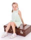 Liten flicka med en stor och mycket gammal resväska. Royaltyfria Bilder