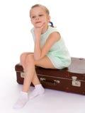 Liten flicka med en stor och mycket gammal resväska. Arkivbild