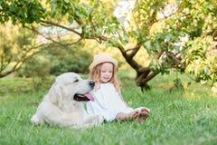 Liten flicka med en stor vit hund i parkera En årig flicka härliga 5 i den vita klänningen kramar hennes favorit- hund under en w royaltyfri bild