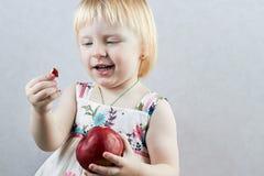 Liten flicka med ett äpple Royaltyfria Foton