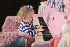 Liten flicka med ett rosa piano Arkivfoto