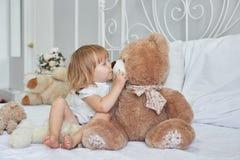 Liten flicka med ett trevligt ljus - brun nallebjörn på vit säng tidigt på morgonen royaltyfri bild