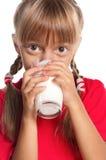 Liten flicka med exponeringsglas av mjölkar Arkivfoton