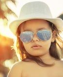 Liten flicka med exponeringsglas och hatten arkivfoto