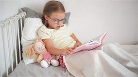 Liten flicka med exponeringsglas som bläddrar igenom en bok, medan ligga i säng Kanske är ett barn sjukt Bredvid henne sitter en  lager videofilmer