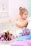 Liten flicka med fågelburen i hemmiljö royaltyfri fotografi