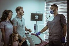 Liten flicka med föräldrar på tandläkarekontrollen royaltyfria bilder