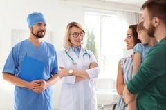 Liten flicka med föräldrar som besöker barns doktorer arkivbild