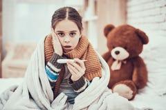 Liten flicka med förkylning i halsduk och filt med termometern i händer hemma arkivfoton