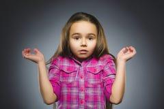 Liten flicka med förvånat uttryck, medan stå mot grå bakgrund royaltyfri bild