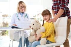 Liten flicka med fadern som besöker barns doktor royaltyfri bild