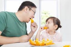 Liten flicka med fadern som äter orangen Arkivbild