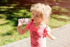 Liten flicka med flaskan av mineralvatten, utomhus- sommar Arkivbild