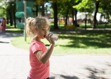 Liten flicka med flaskan av mineralvatten, utomhus- sommar Royaltyfri Fotografi