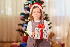 Liten flicka med gåvan i julhatt av Santa Claus med en gif Fotografering för Bildbyråer