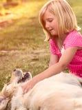 Liten flicka med golden retrieverhunden Royaltyfri Bild