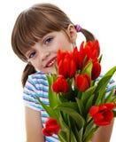 Liten flicka med gruppen av nära övre för röda tulpan Royaltyfri Foto