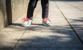 Liten flicka med gymnastikskor och leggins som utomhus utbildar Arkivfoton