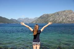 Liten flicka med händer upp på den Kotor för sommarsemester fjärden måndag royaltyfri bild