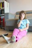 Liten flicka med hållande ögonen på TV för TVfjärrkontroll Arkivfoto