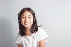 Liten flicka med hörlurar Arkivbild