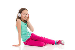 Liten flicka med hörlurar som tycker om musiken Arkivbild