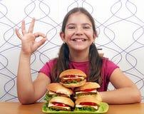 Liten flicka med hamburgare och oj handtecken Royaltyfri Fotografi